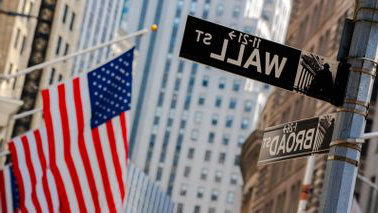 Wall Street 和 Broad Street signs with an American flag in the background
