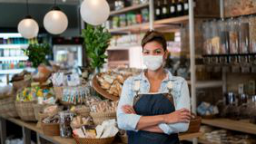 female small business owner in store wearing a face mask