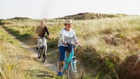 couple riding bikes in an open field