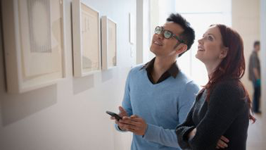 Couple starting to invest in art looking at a piece