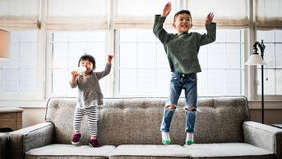 brother 和 sister jumping on the couch playfully