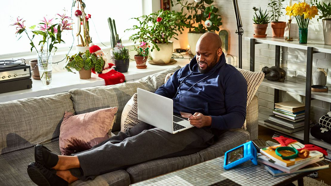 Man lounging on a sofa with his feet up using a laptop computer