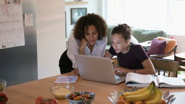 mom 和 daughter working on FAFSA in kitchen