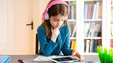 Young girl doing online learning through educational websites 和 apps for kids