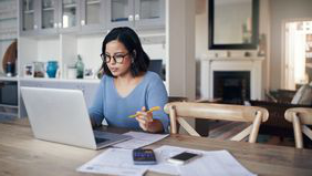Woman working on her finances on a laptop.