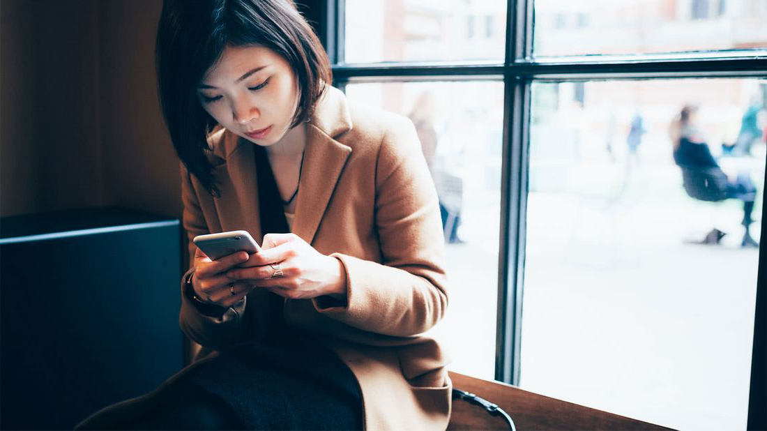 Woman on her phone researching how to manage debt