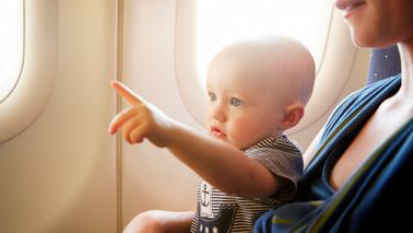 baby on plane pointing