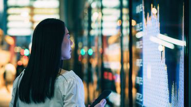 A young woman checking out stock charts from the street