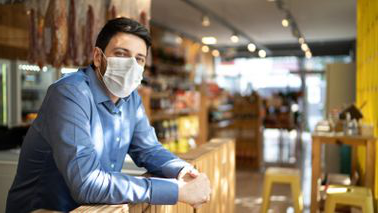 Male business owner 和 PPP loan recipient wearing a face mask
