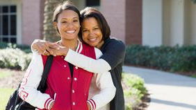 smiling mother hugging college-aged daughter
