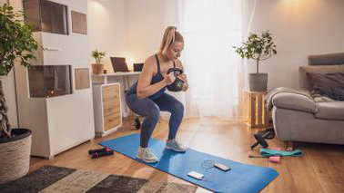 Woman staying motivated to work out at home while social distancing.