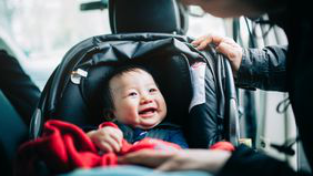 baby being strapped into car seat