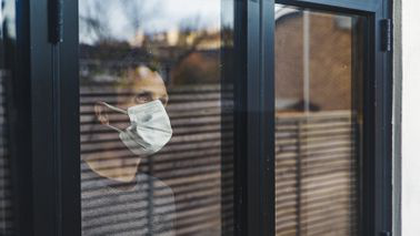 Man wearing mask while looking out window.