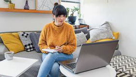 woman sitting on couch working on laptop