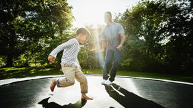 Father 和 young son jumping on trampoline