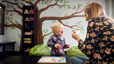 nanny playing with small child in playroom
