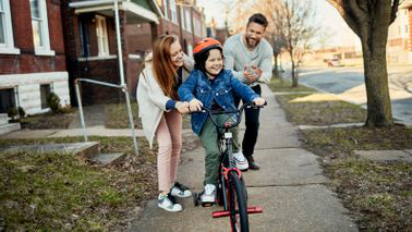 Mom and dad pushing child on a bike, pondering who should be the trustee 和 guardian for their child.