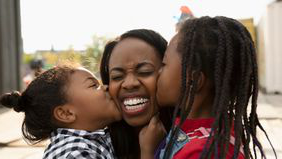 young daughters kissing mom on cheek
