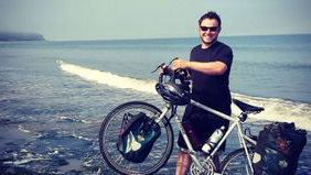 Man 和 bike on a beach after he quit his job to travel full-time