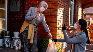 Volunteer bringing groceries to a senior woman at home during the coronavirus