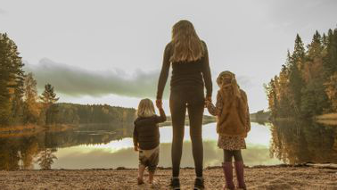 Mother 和 her daughters looking at a lake.