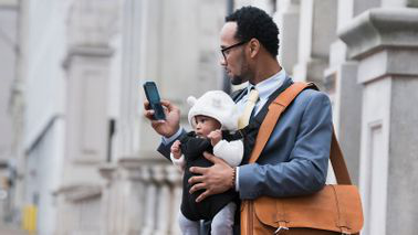 Dad looks at phone with a baby in carrier.