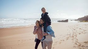 Couple walking on the beach with their daughter after learning how whole life insurance works.