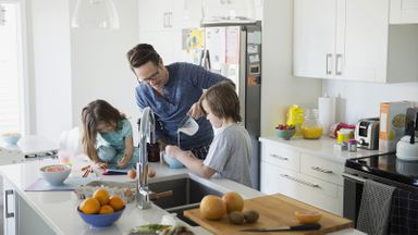 Dad cooking with his kids after learning about disability insurance