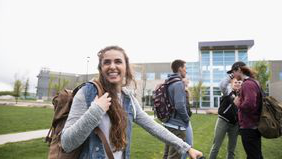Young female college student smiling 和 walking on campus.