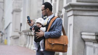 A business man checking his phone while holding a baby