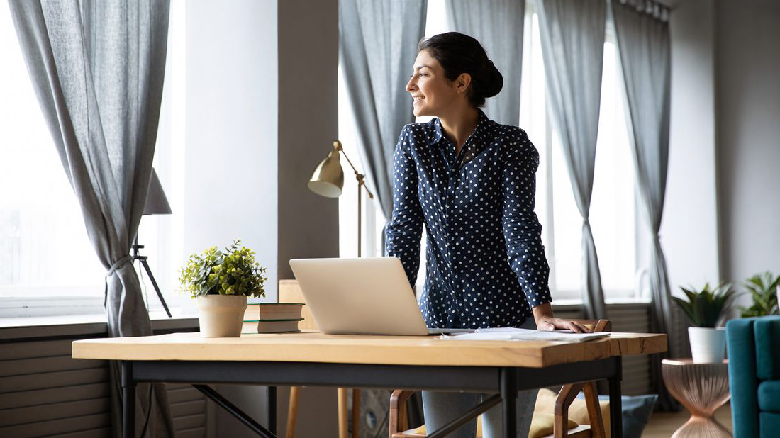 woman smiling while looking out window and st和ing at desk