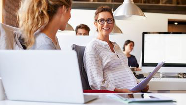 Pregnant businesswoman holding documents in office