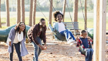 Family on swings at park.