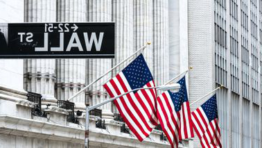 New York Stock Exchange with American flags 和 Wall Street sign