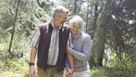 Couple walking in the forest discussing how to start planning for retirement.