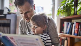 A father reading a book to his young daughter